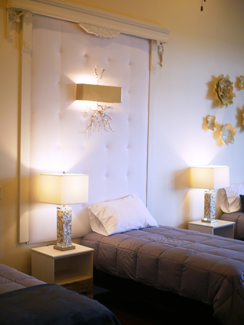 beautiful cream colored bedroom with 3 beds and lamps with square ivory shades