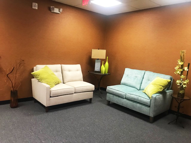 tan room with grey carpet and 2 love seats with yellow pillows