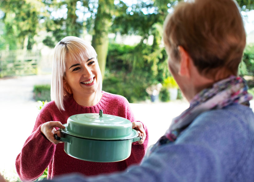 young blonde woman bringing casserole to elderly neighbor at front door - support