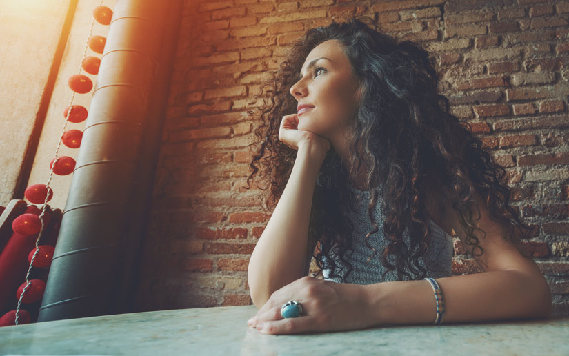 beautiful woman with curly dark hair looking thoughtfully out of cafe window - mind