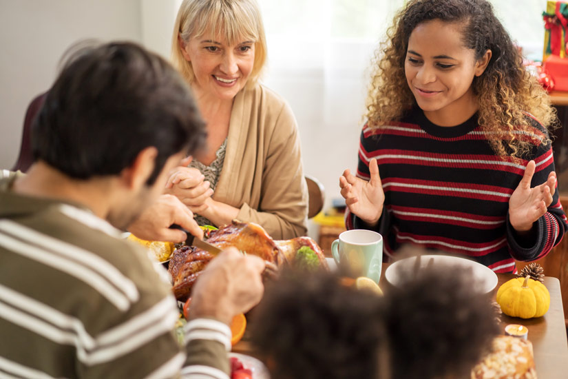 family enjoying thanksgiving meal together - thanksgiving