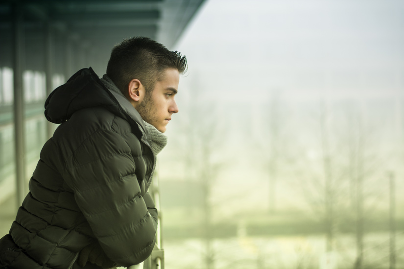 young man standing on balcony during winter looking sad - seasonal affective disorder