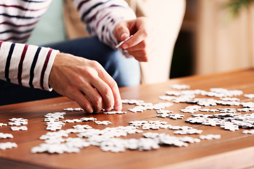 closeup of young man doing a jigsaw puzzle - hobbies
