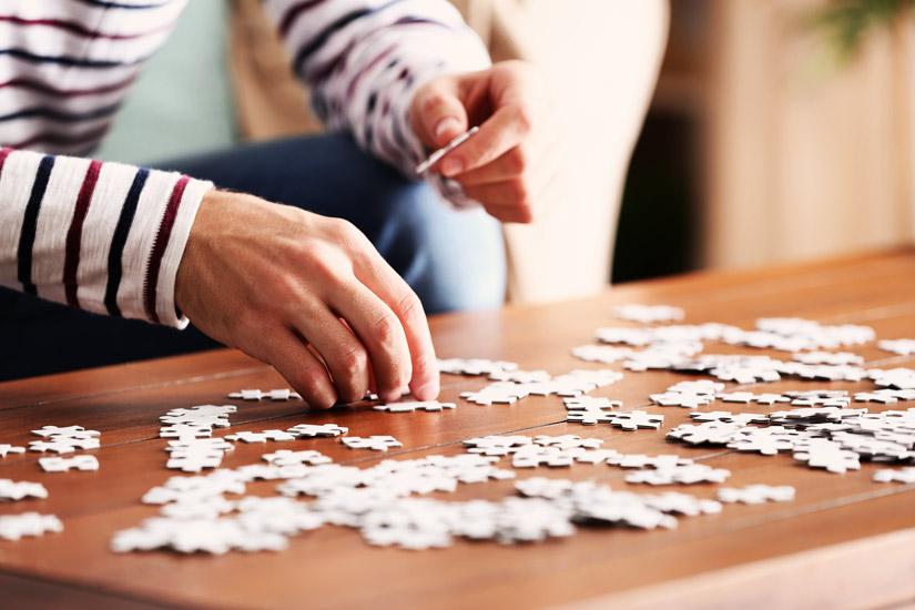 closeup of young man doing a jigsaw puzzle - hobbies