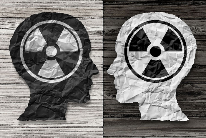 black and grey illustration of two heads with radiation symbol on them - toxic relationships