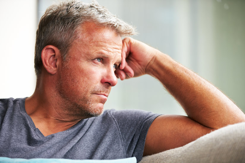 handsome middle age man sitting at home thinking - caring