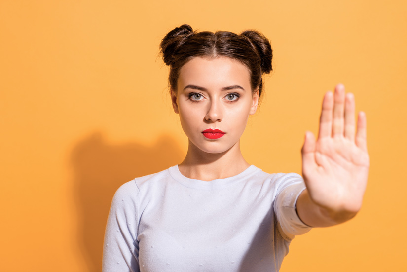 pretty young woman on yellow background holding hand up in 'stop' gesture - excuses
