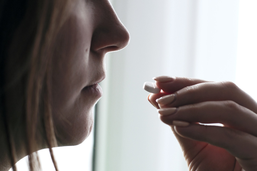closeup of woman taking a white pill - chronic pain