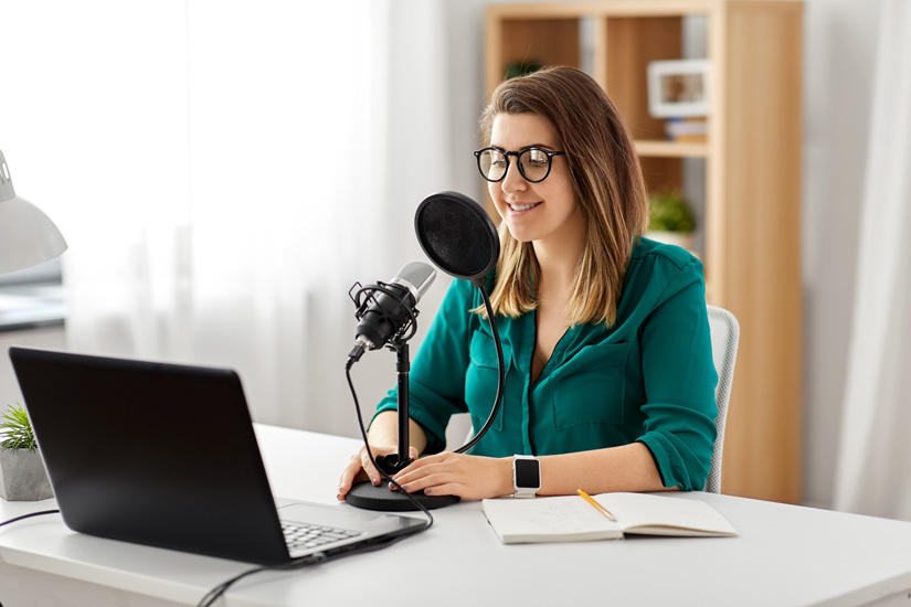 woman recording a podcast - recovery-related podcasts