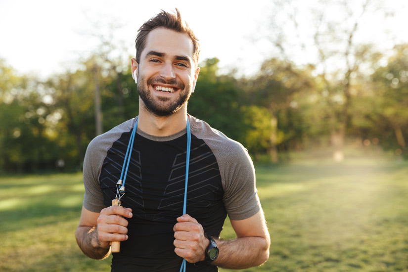 smiling young man at park with jump rope around his neck - lifestyle changes
