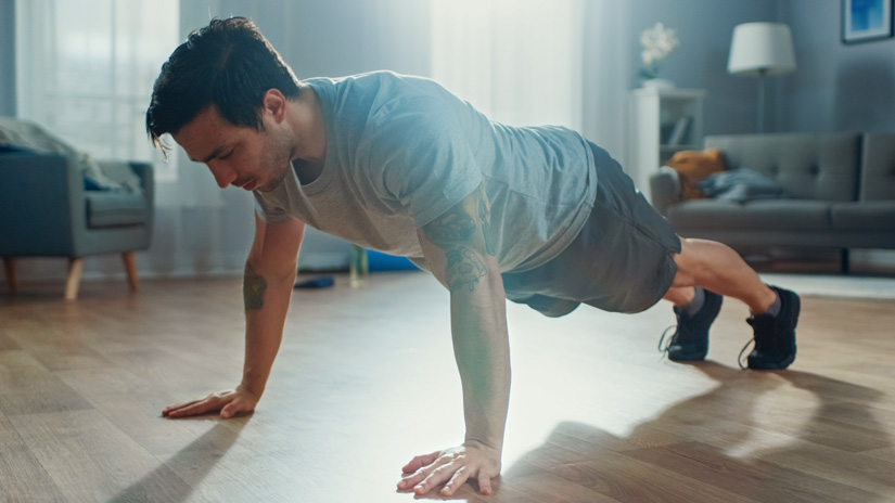 dark haired man doing push ups at home - exercise