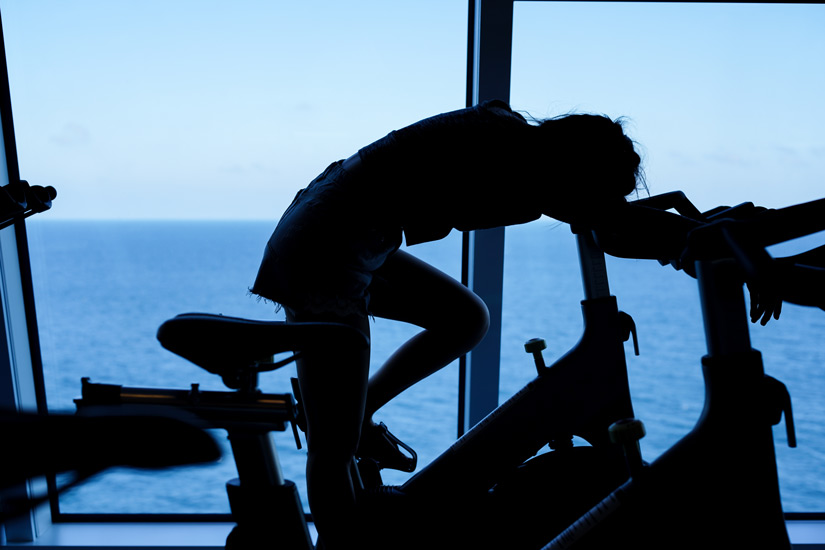 silhouette of exhausted woman on stationary bike - substitute addictions