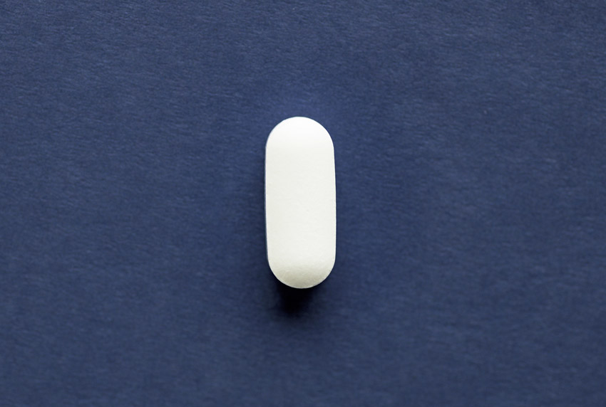white oblong tablet on dark blue paper background - Xanax
