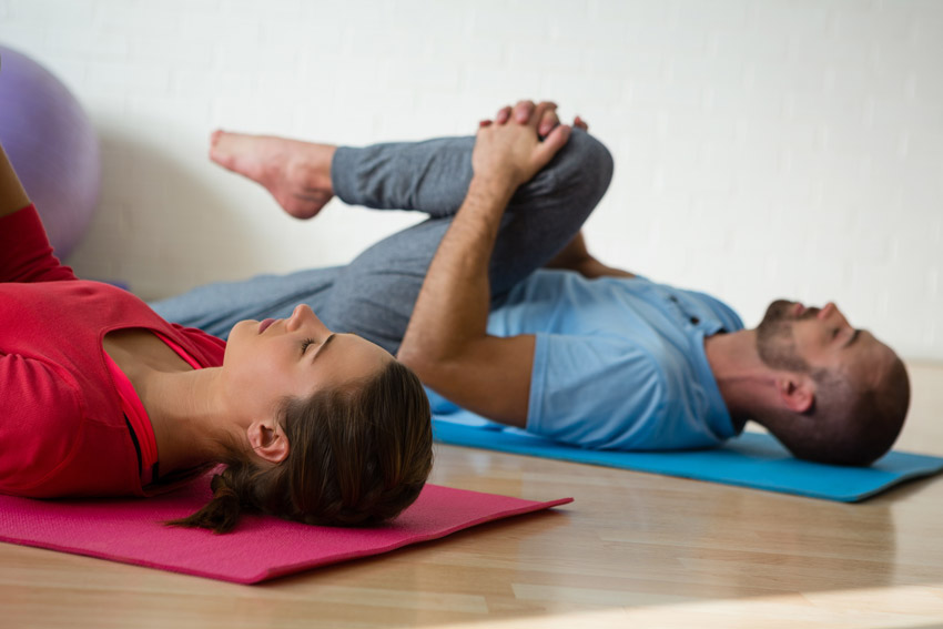 attractive couple doing yoga stretches - recovery yoga