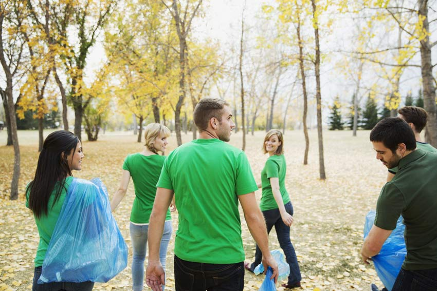 group of young adults cleaning up trash in a park - guilt