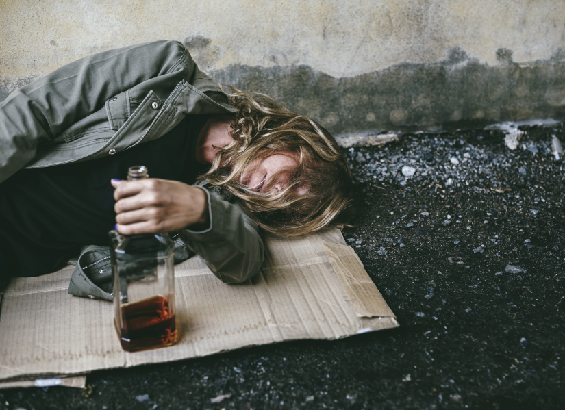 Homeless woman lay down on the ground holding alcohol - Help
