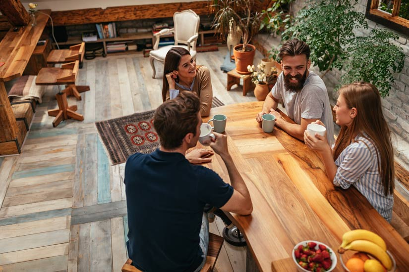 group of four friends visiting over coffee at a table in a cafe or restaurant - misconceptions