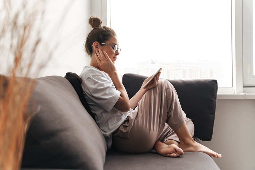 pretty young woman sitting on the couch at home looking at her smart phone, relaxing alone - newly sober